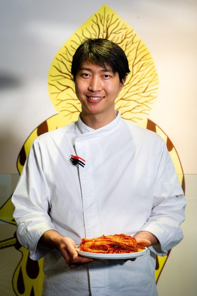 las manos de Luke Jang con un plato de kimchi coreano